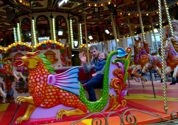 Saturday is caption day, Amy's first ride on a merry-go-round