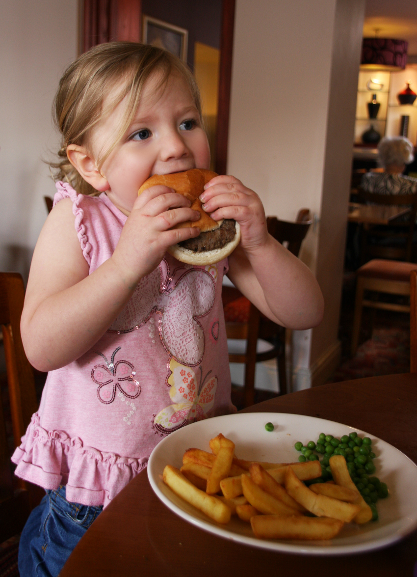 Amy eating a burger from the kids menu Blue Bowl Hanham Bristol Sizzling Pub